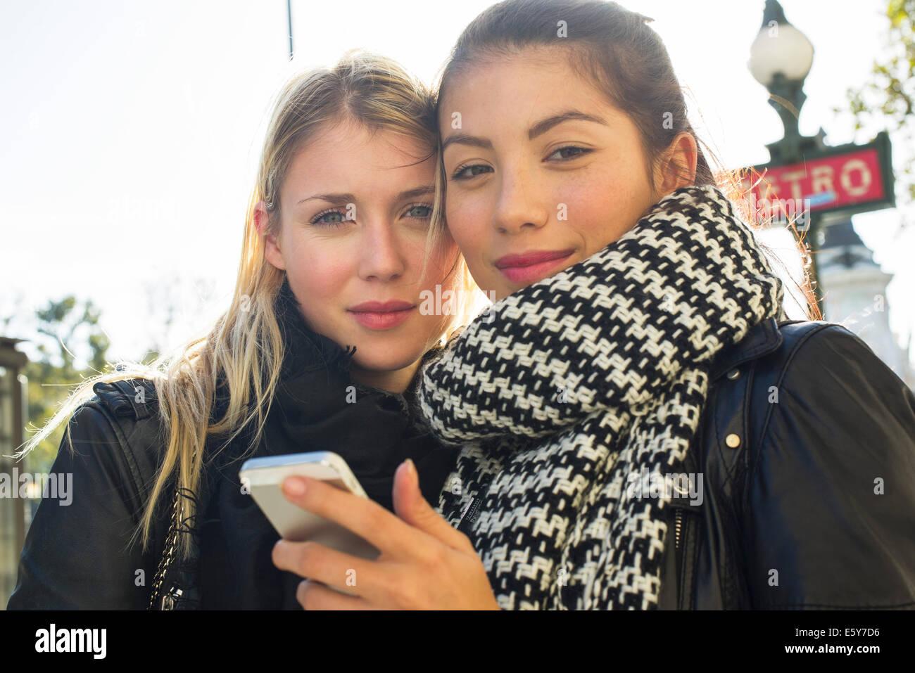 Junge Frauen, die im freien Blick auf Handy zusammen Stockbild