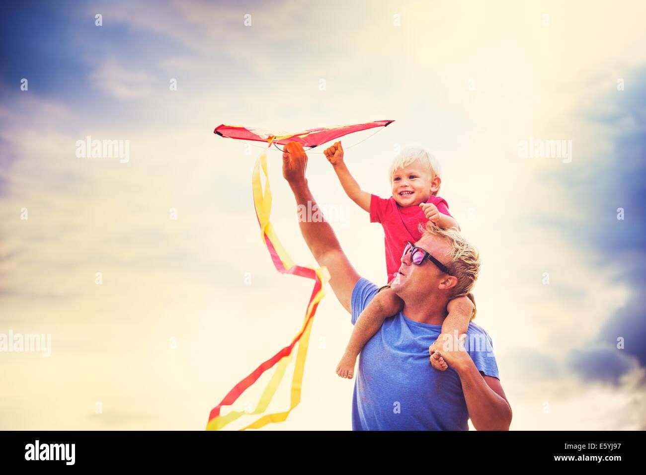 Sohn des Vaters Schulter bei Sonnenuntergang einen Drachen zusammen Stockbild