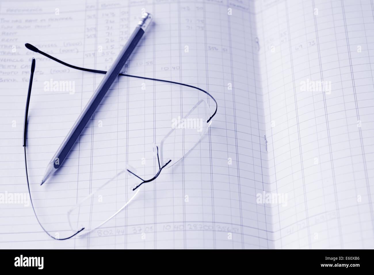 Brille und einem Bleistift auf jährliche Einkommensteuer Bericht Buchführung lesen. Konzept-Foto von Steuer, Stockbild
