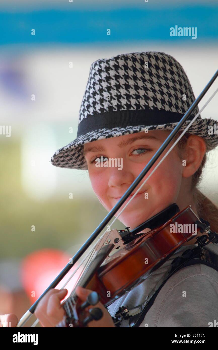 Ein junges Mädchen ist mit ihrer Violine in Fremantle, Western Australia als Straßenmusikant. Stockbild