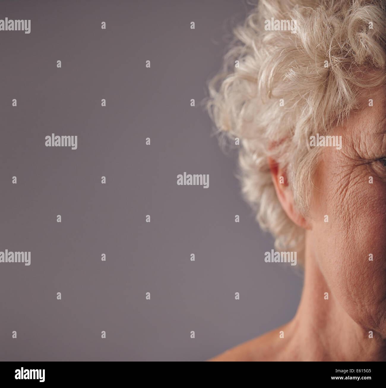 Ältere Frau Gesicht mit faltige Haut auf grauem Hintergrund abgeschnitten. Krähenfüße auf Augen der alten Frau. Stockfoto