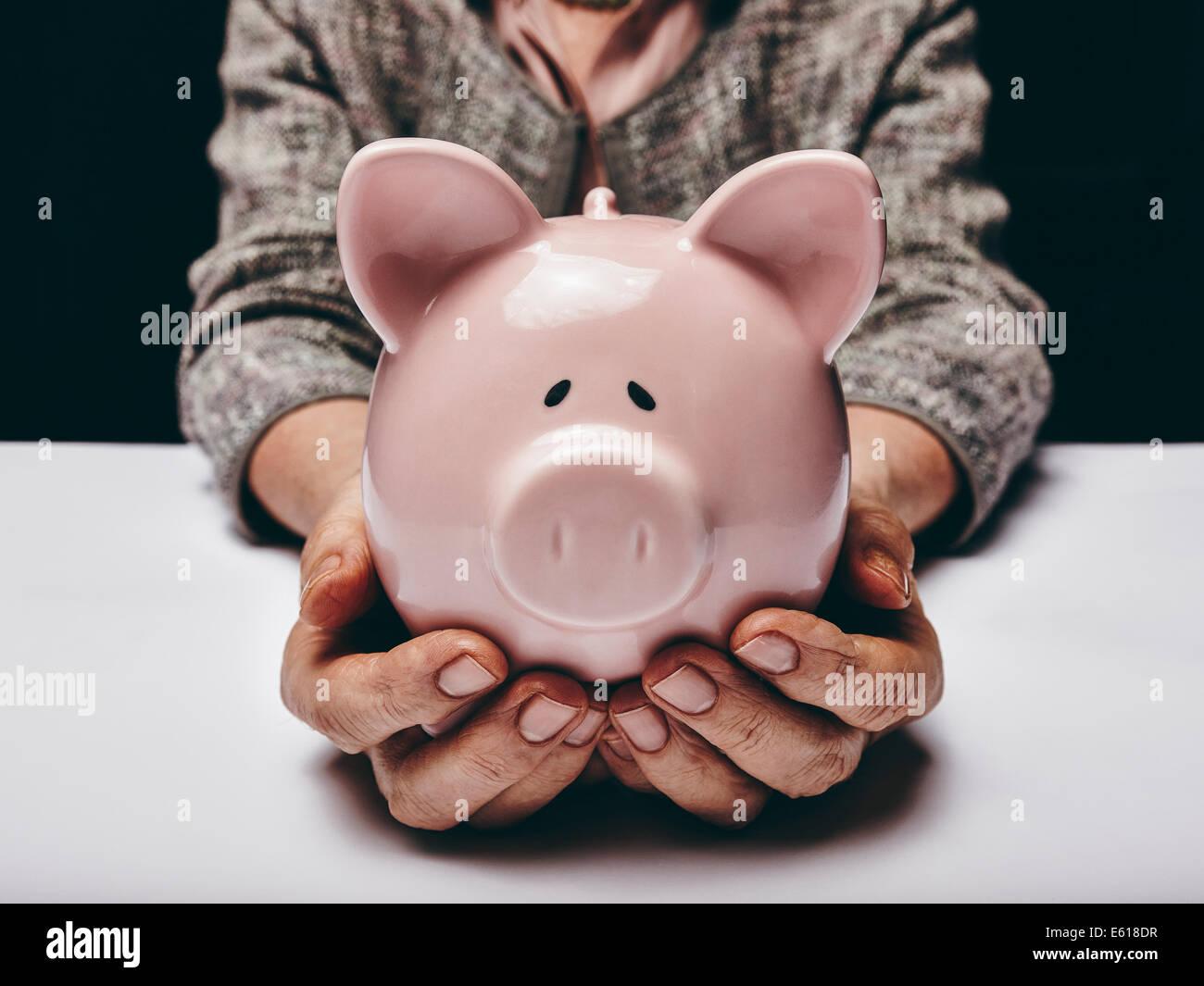 Nahaufnahme der älteren Frau mit rosa Schwein Spardose. Ältere Frau Hände halten ein Sparschwein. Stockbild