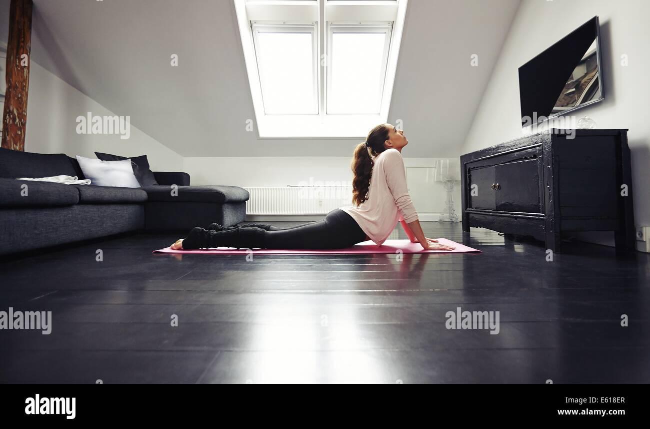 Junge Brünette Frau Dehnübungen Erdgeschoss erarbeiten. Fitness weibliches Modell Training auf der Matte zu Hause. Stockfoto