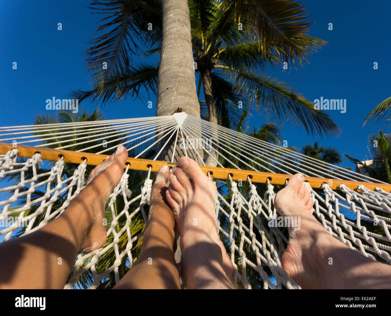 Füße des Paares in der Hängematte unter Palmen Stockbild