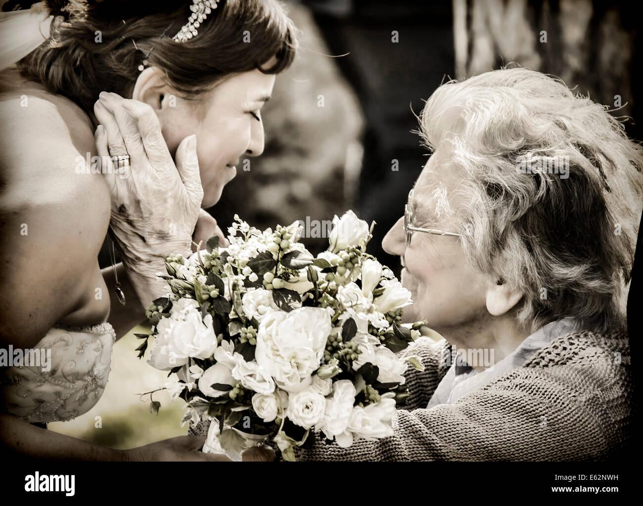 Eine Großmutter begrüßt und beglückwünscht ihre Enkelin an ihrem Hochzeitstag Stockbild