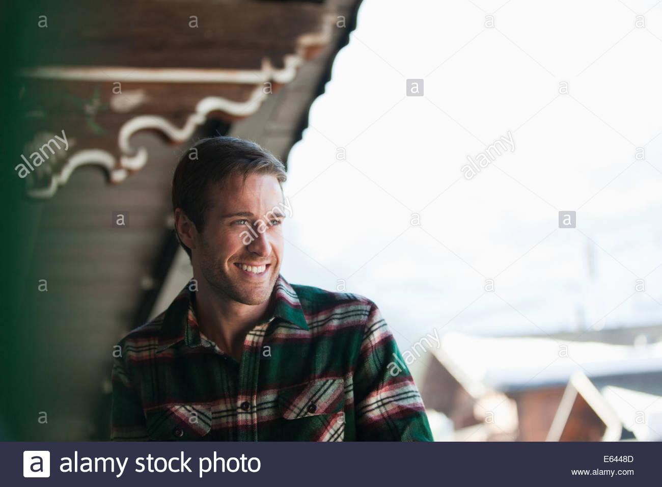 Mann lachend auf der Veranda der Hütte Stockbild