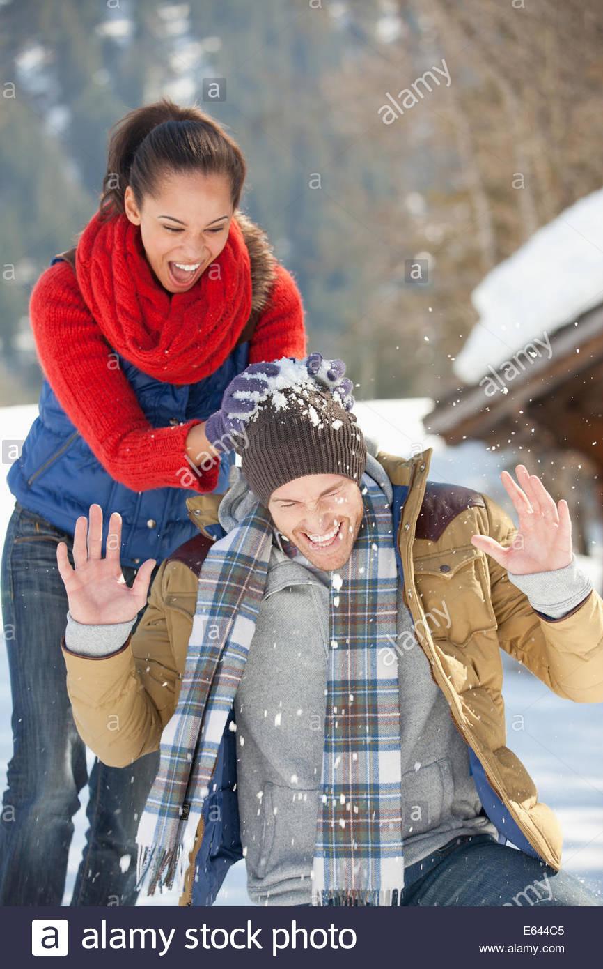 Frau brechen Schneeball über ManKopf Stockbild