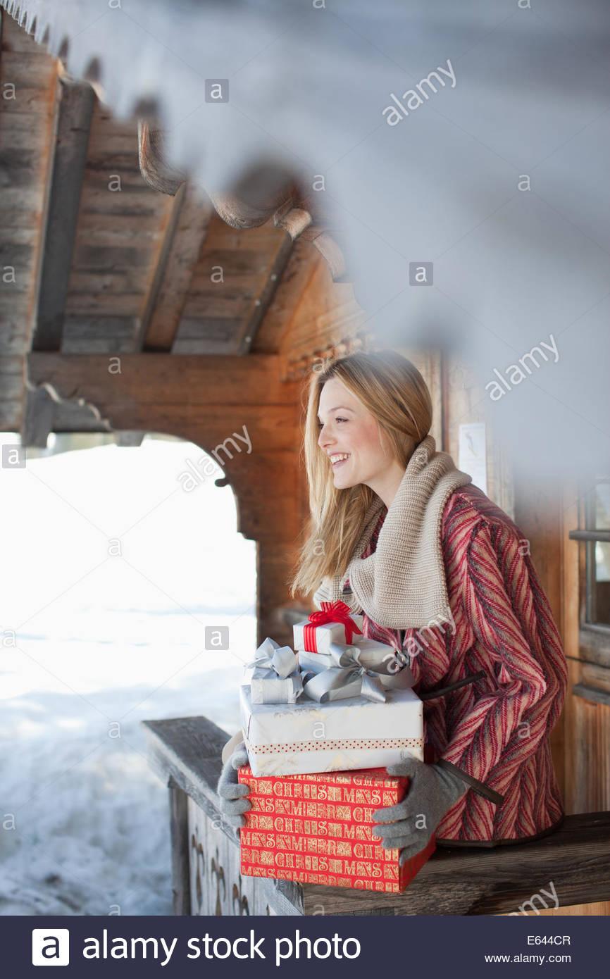 Lächelnde Frau hält Weihnachtsgeschenke auf Kabine Veranda Stockfoto ...
