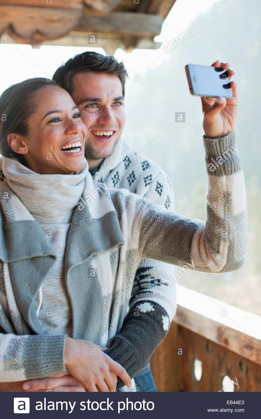 Lächelnde paar Einnahme Selbstbildnis mit Kamera-Handy auf Kabine Veranda Stockbild