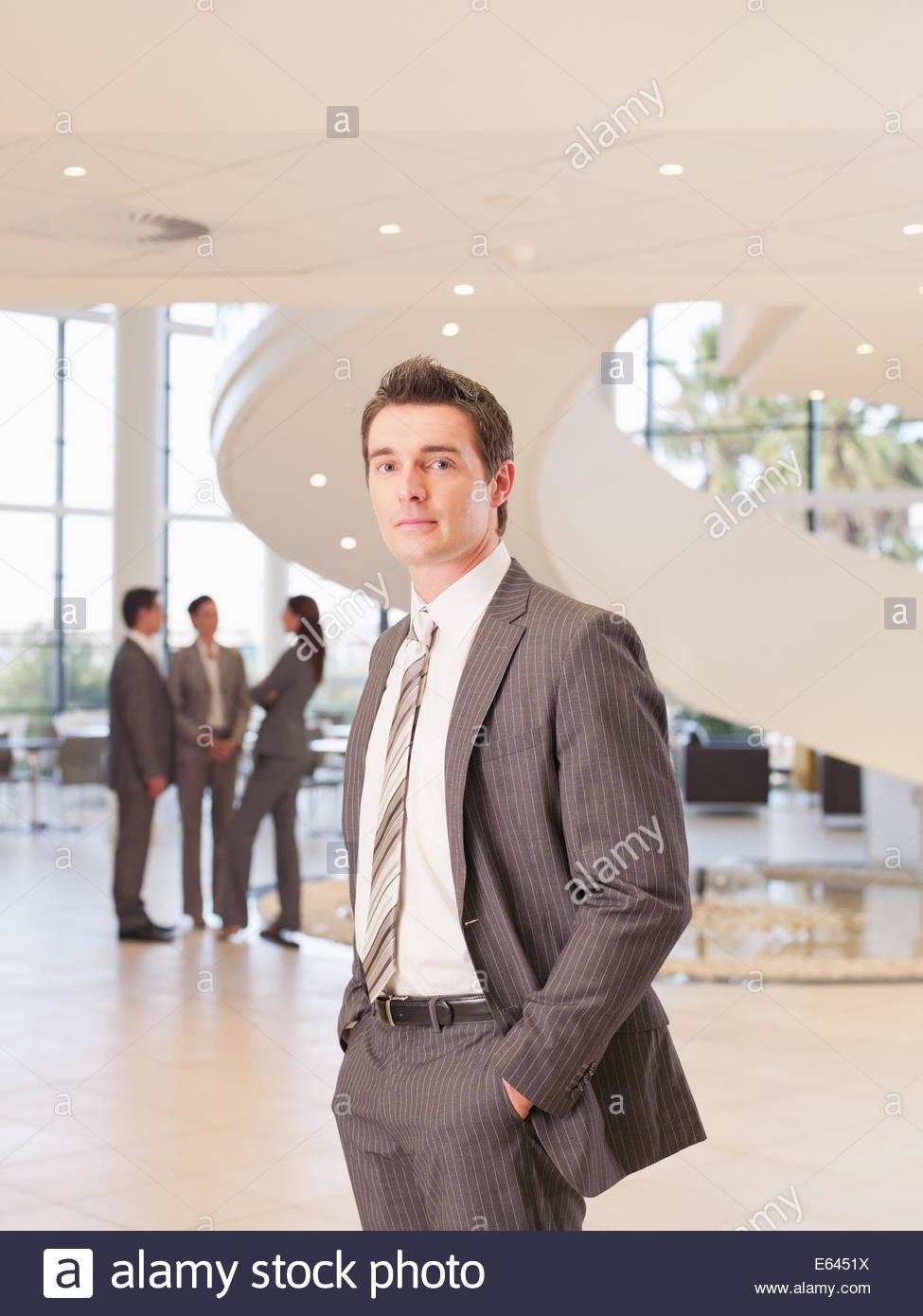 Geschäftsmann, stehend im Büro lobby Stockbild