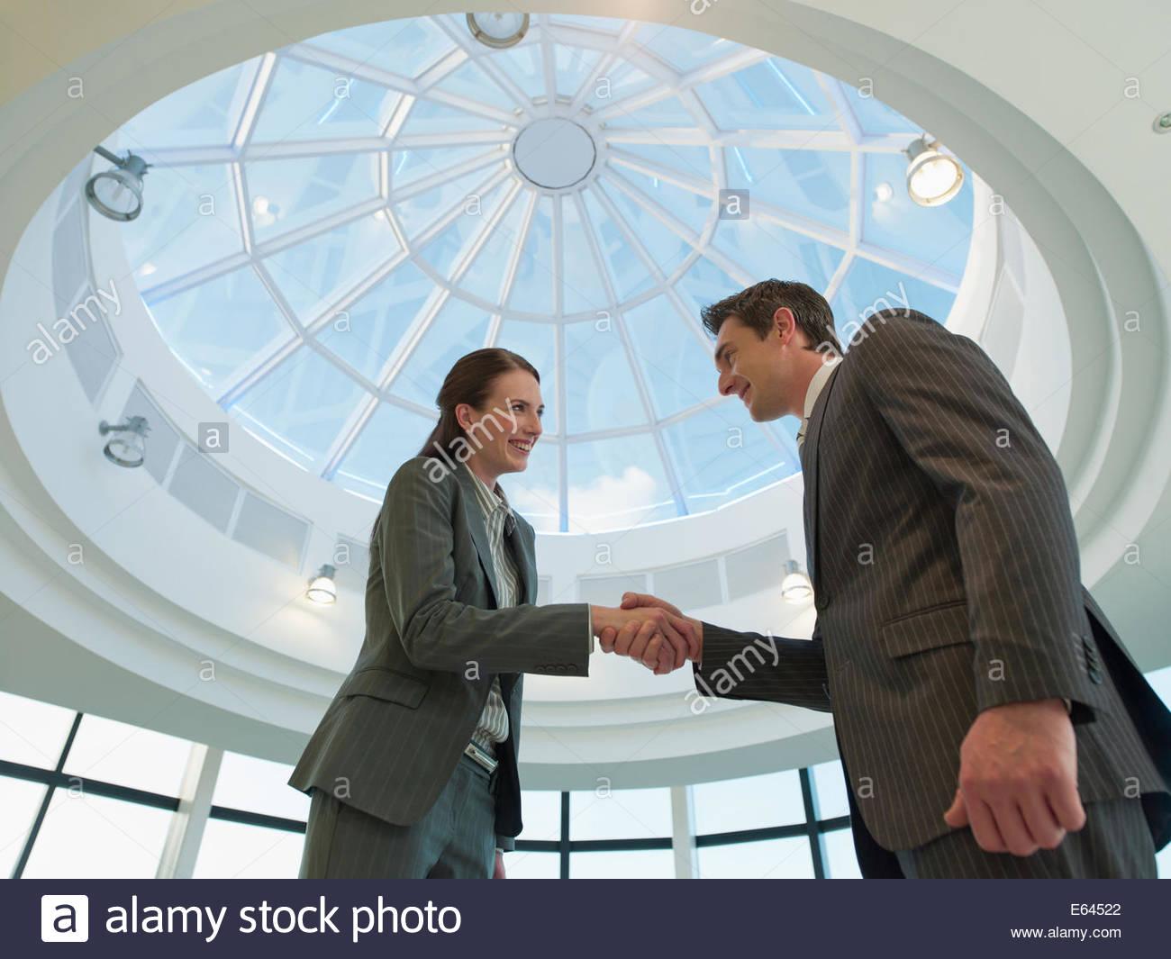 Geschäftsleute Händeschütteln im Büro Stockbild