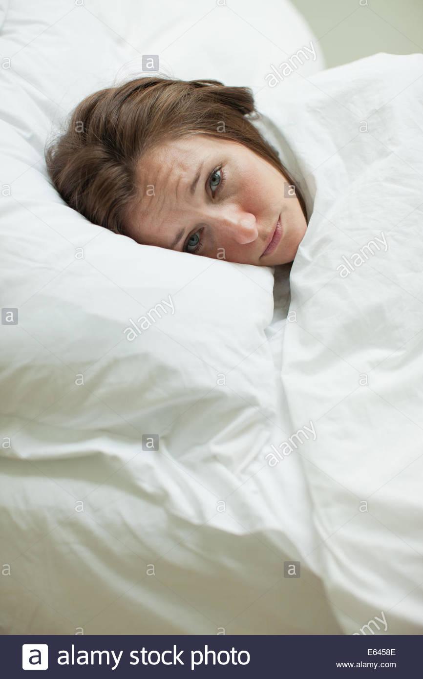 Kranke Frau im Bett unter der Decke Stockbild