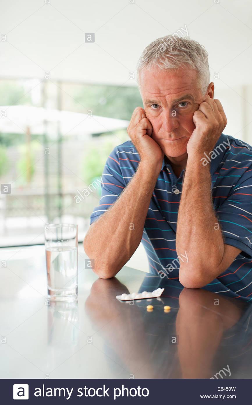 Unglücklicher Mensch betrachten Pillen auf Zähler Stockbild
