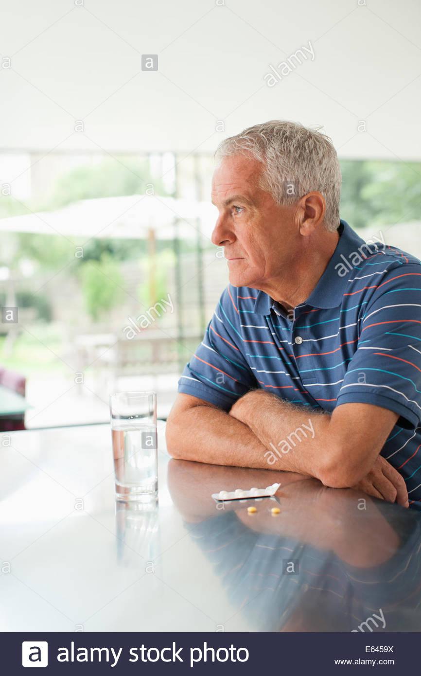 Unglücklicher Mensch nach draußen mit Pillen auf Theke Stockbild