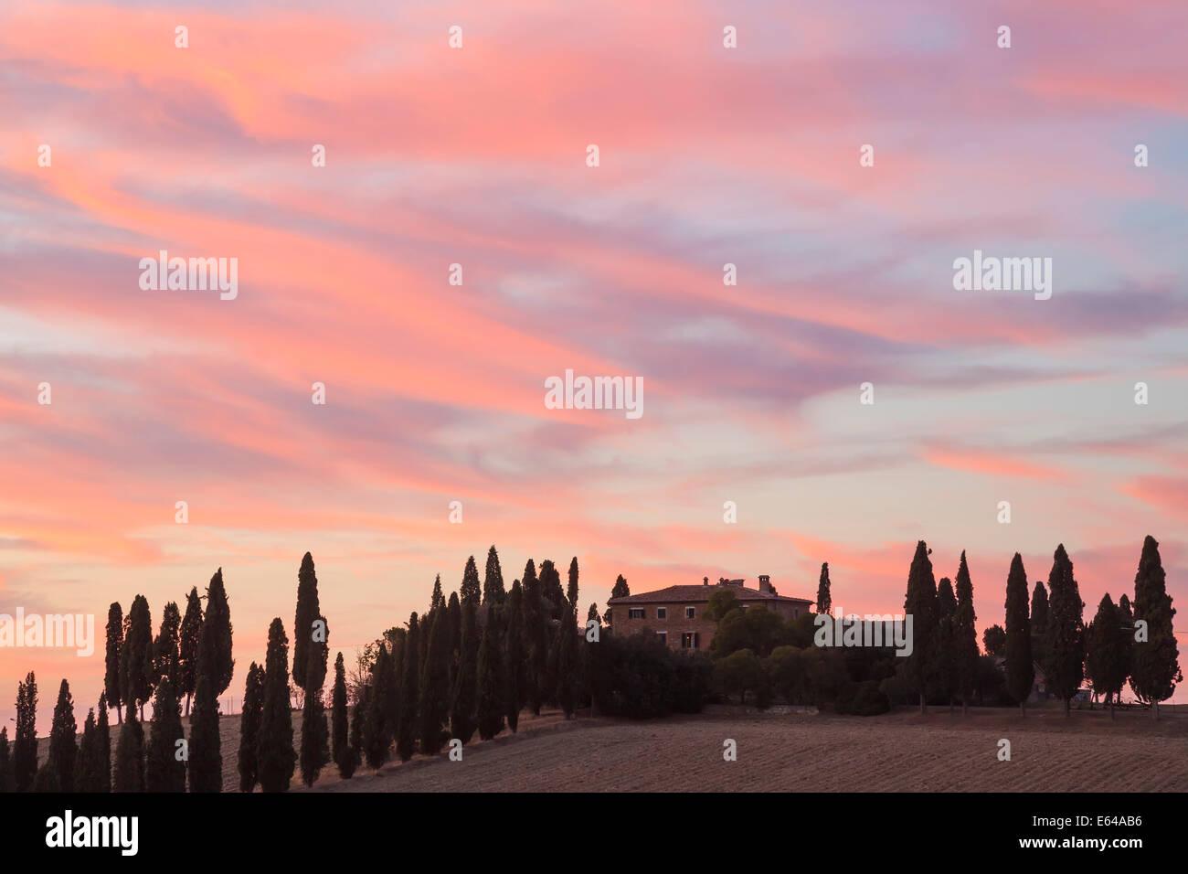Bauernhaus und Zypresse Bäume bei Sonnenuntergang, Toskana, Italien Stockbild