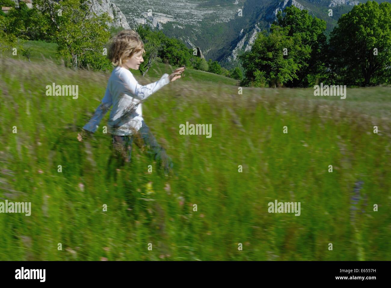 93422bec2e47fb Kleines Mädchen läuft durch eine Wiese Stockfoto