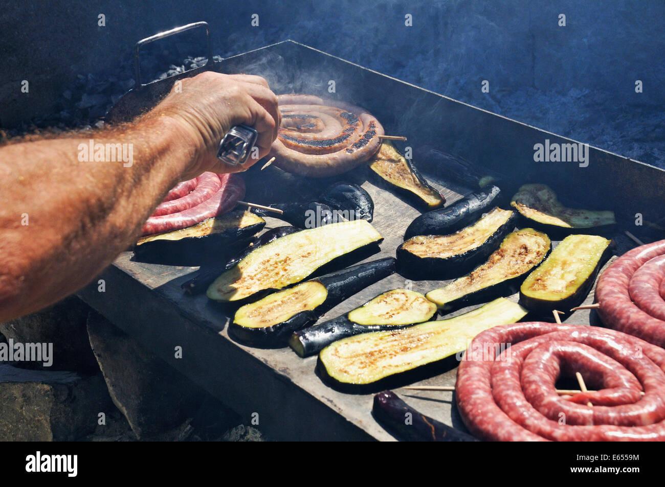 Würstchen und Auberginen/avocado Kochen auf einem Grill BBQ Stockbild