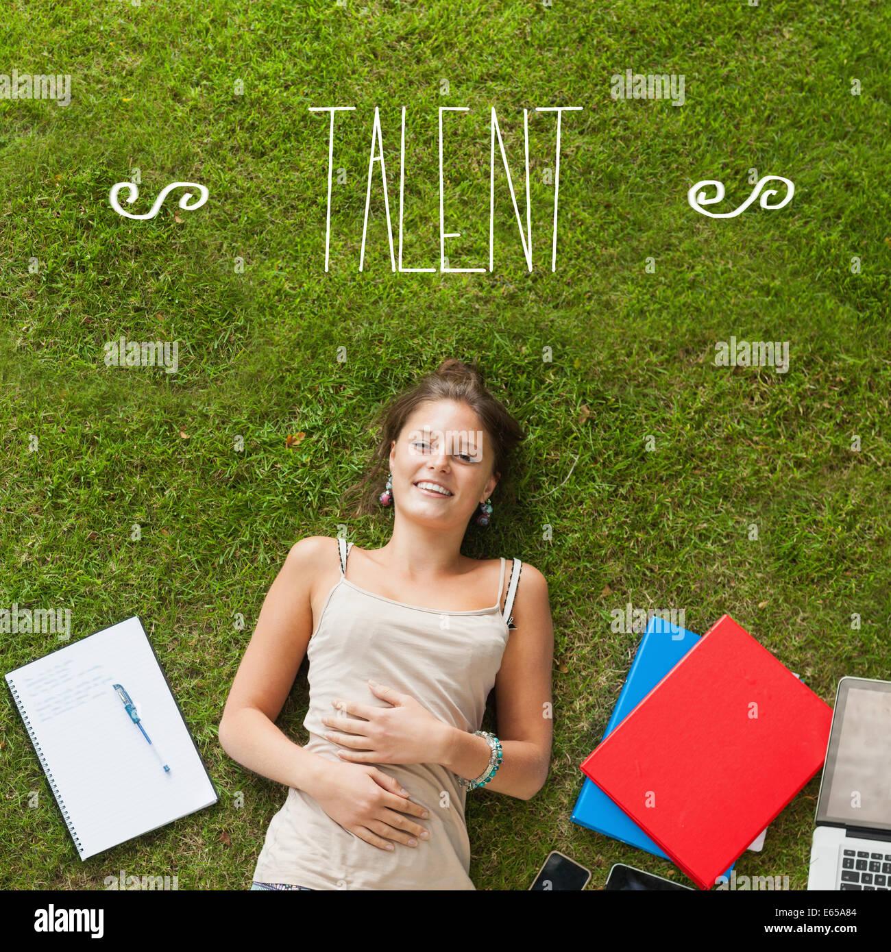 Talent gegen hübsche Studentin liegen auf dem Rasen Stockbild