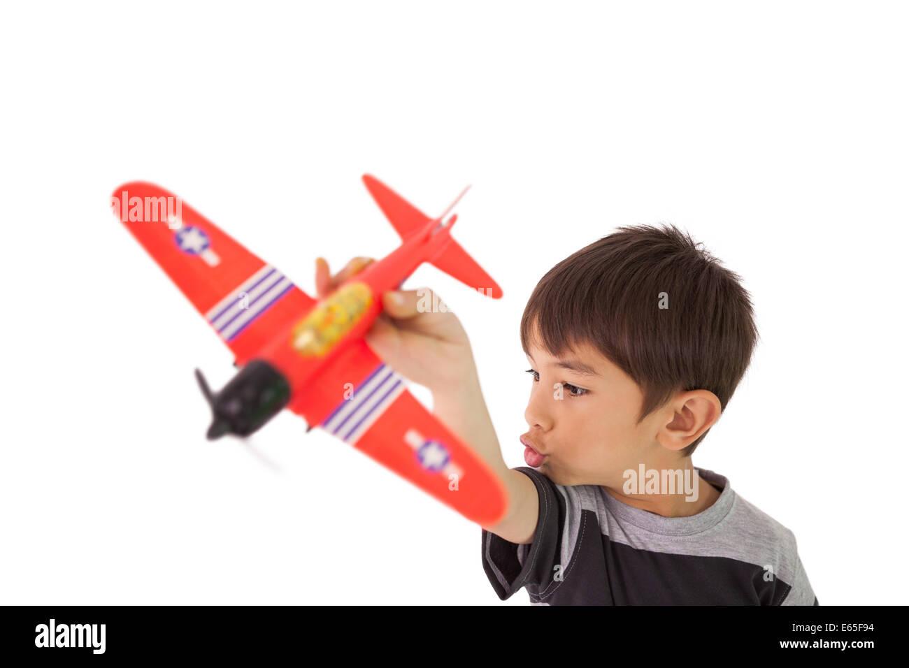 Glückliche kleine Junge spielt mit Spielzeugflugzeug Stockbild
