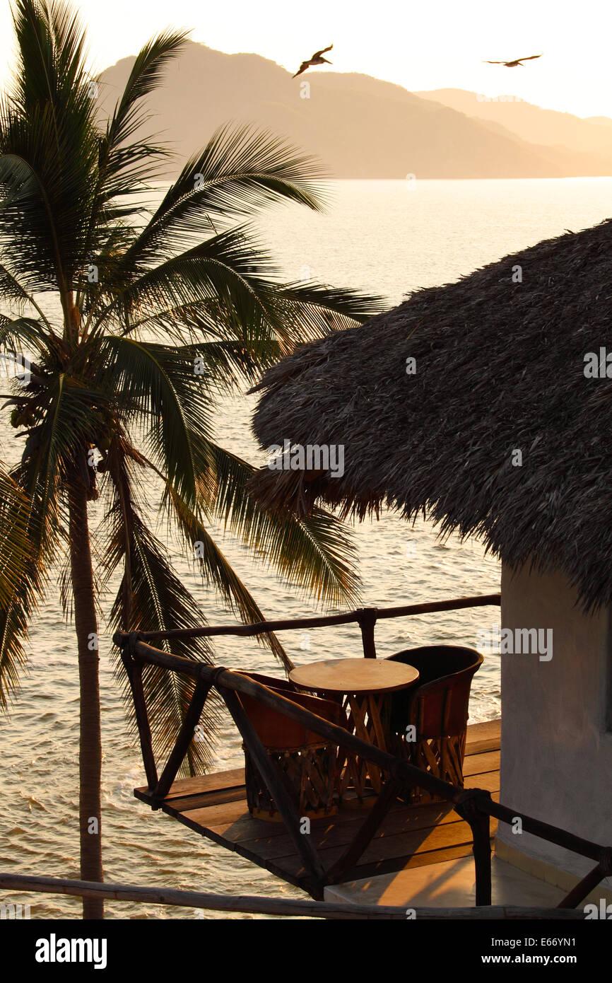 Tisch und Stühlen mit Blick auf den Ozean auf einem Balkon aus Holz in Manzanillo, Colima, Mexiko. Stockbild