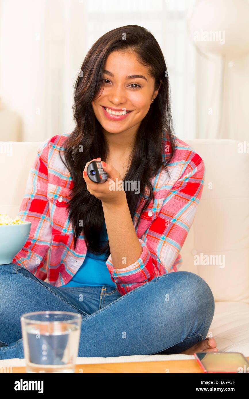 Hispanic Frau vor dem Fernseher auf sofa Stockfoto