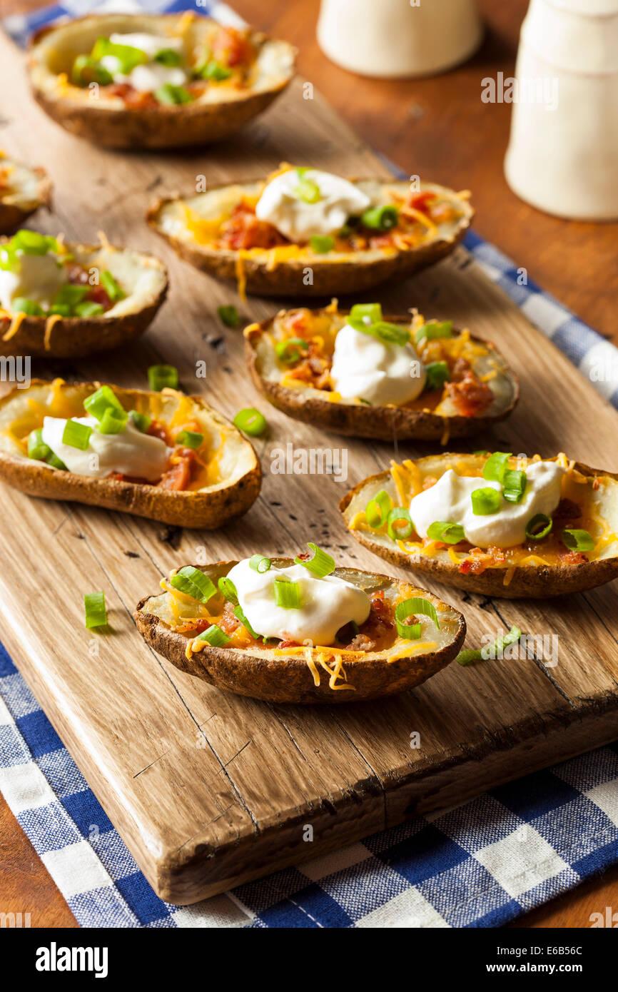 Hausgemachte Kartoffelschalen mit Speck, Käse und Sauerrahm Stockbild
