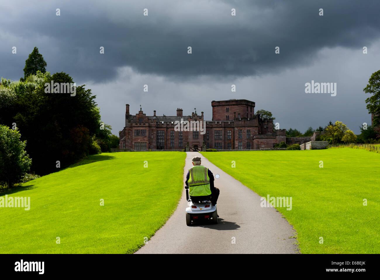 Mann auf Mobilität Roller nähert sich Greystoke Schloß, Cumbria, England UK Stockbild