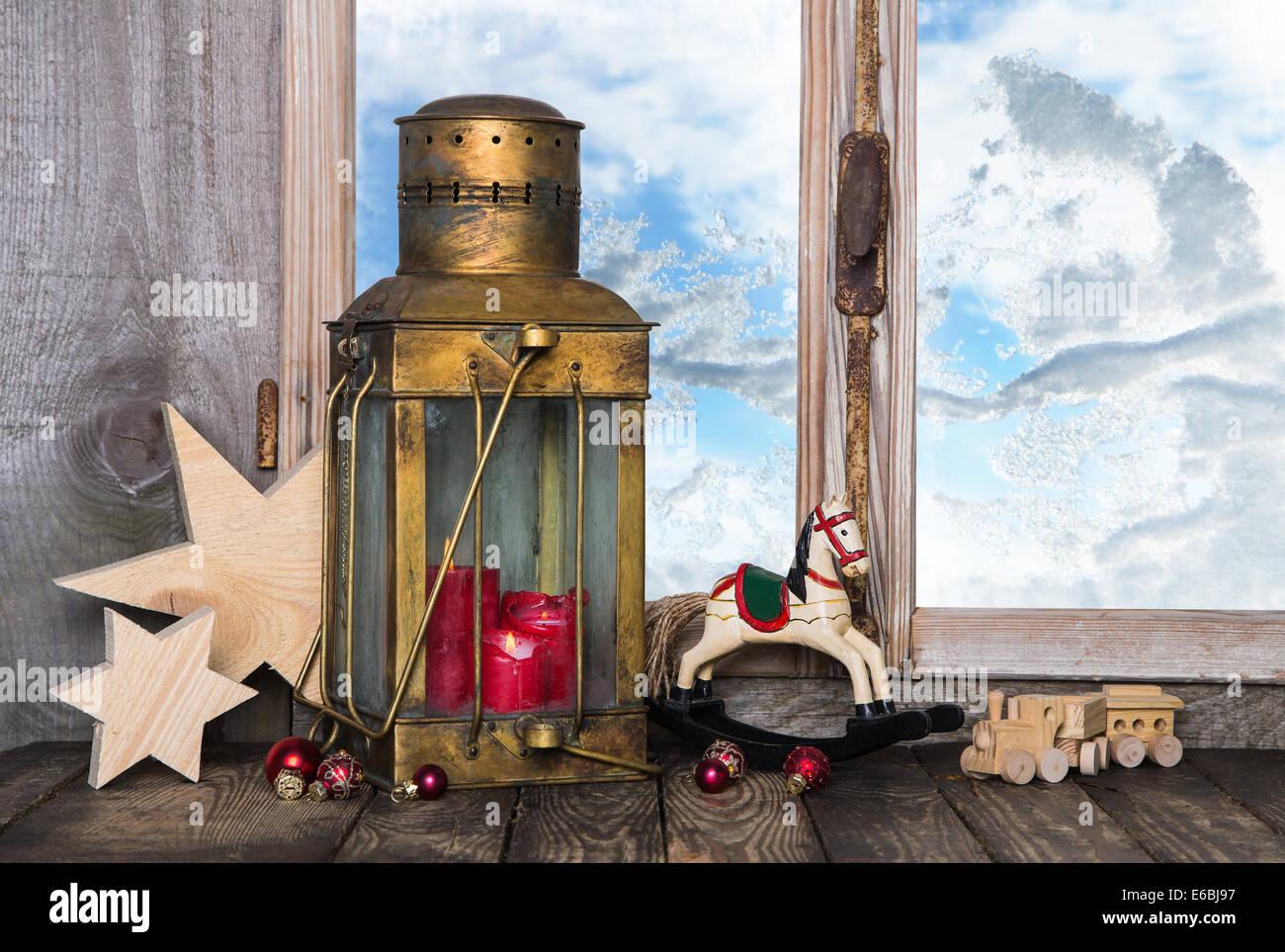 Nostalgische alte Weihnachts-Dekoration mit alten Spielsachen und eine alte Laterne mit Kerzen auf der Fensterbank. Stockbild