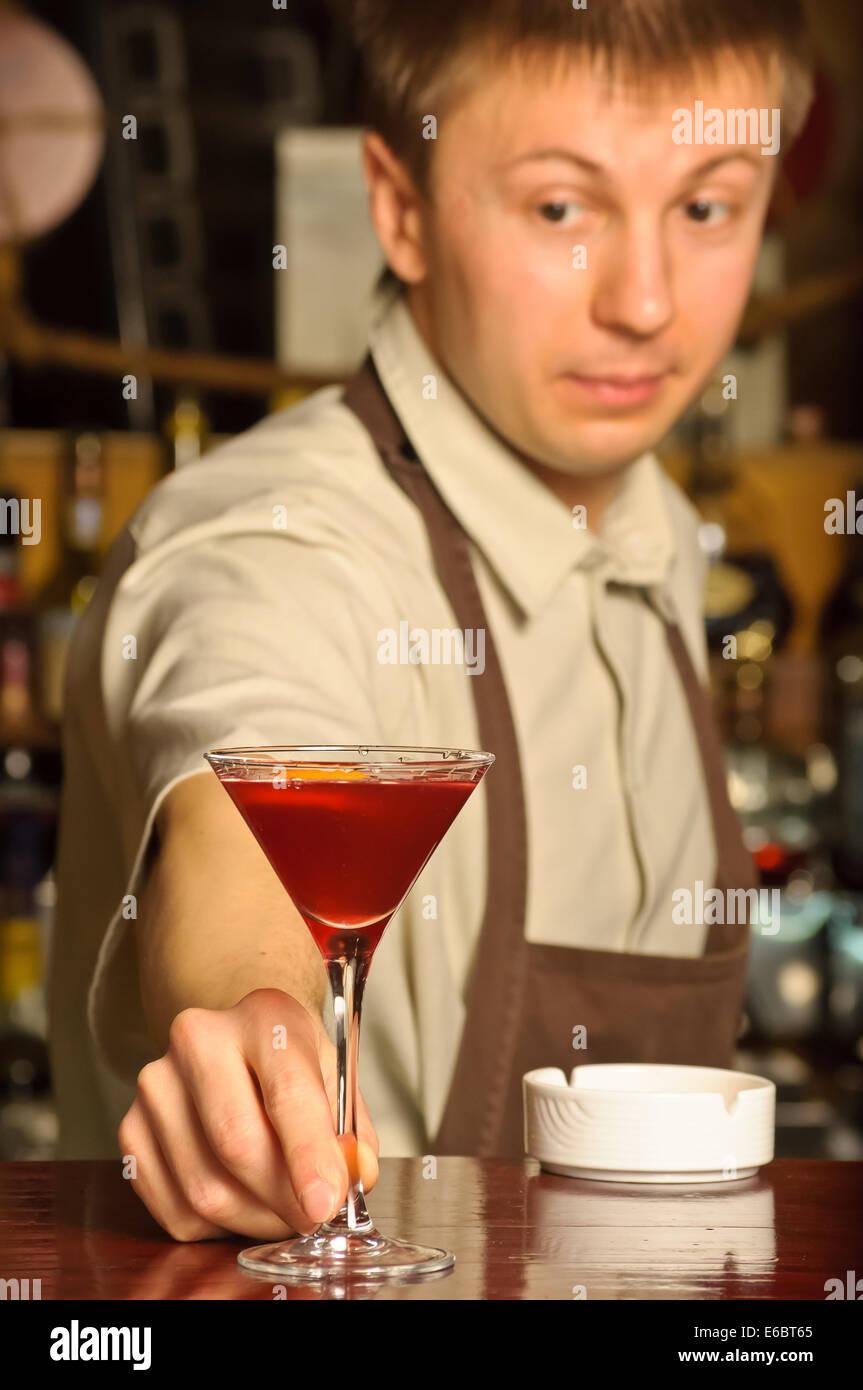 Barkeeper halten Sie das Glas mit Cocktail - drinnen Stockbild
