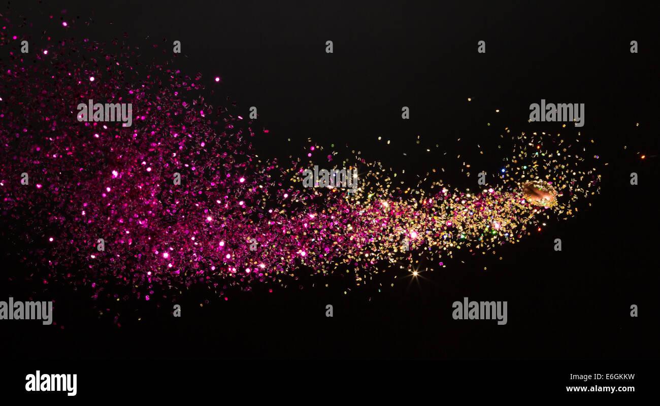 Mischen von Pulver Farbe und Glitter erfasst Mid-flight in hoher Geschwindigkeit, da es Schießen aus einer Stockbild
