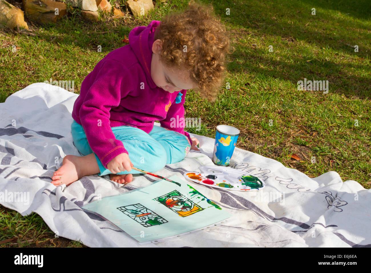 junge dreijährige malen im freien Stockfoto