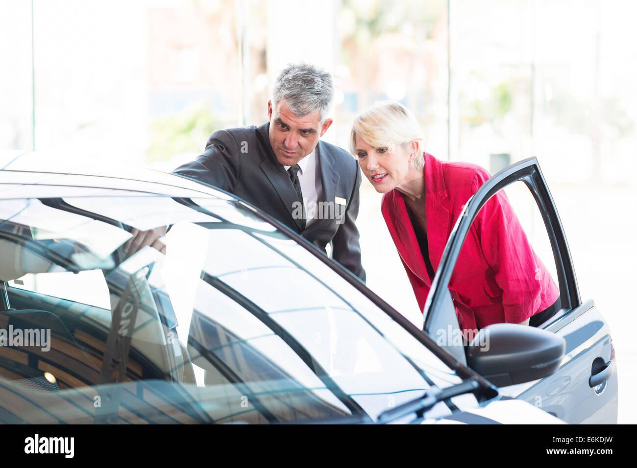Mitte Alter Verkäufer zeigt neues Auto zu potenziellen Kunden Stockbild