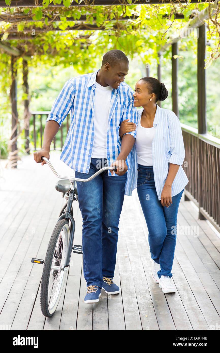 junge afrikanische amerikanische paar zu Fuß mit dem Fahrrad unter Weinreben Stockbild