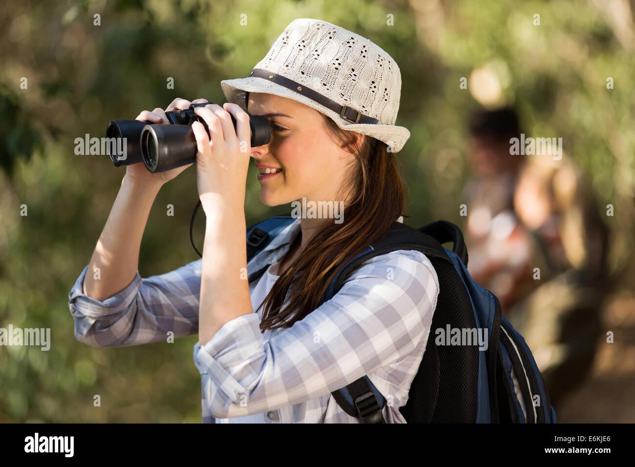 Fröhliche junge frau mit fernglas vogelbeobachtung im wald