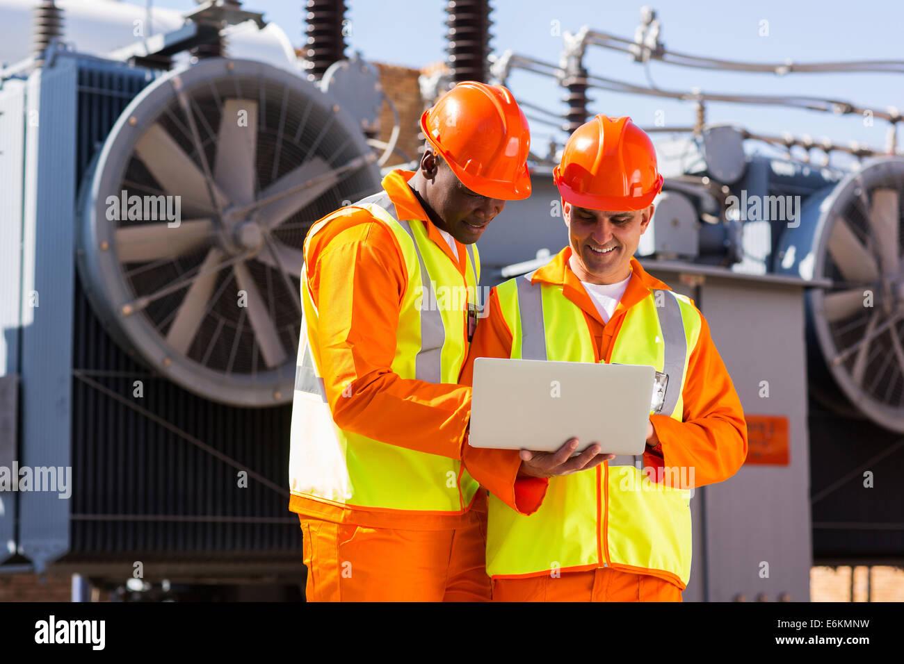 Elektroingenieure mit Laptop-Computer in elektrische Unterstation Stockbild