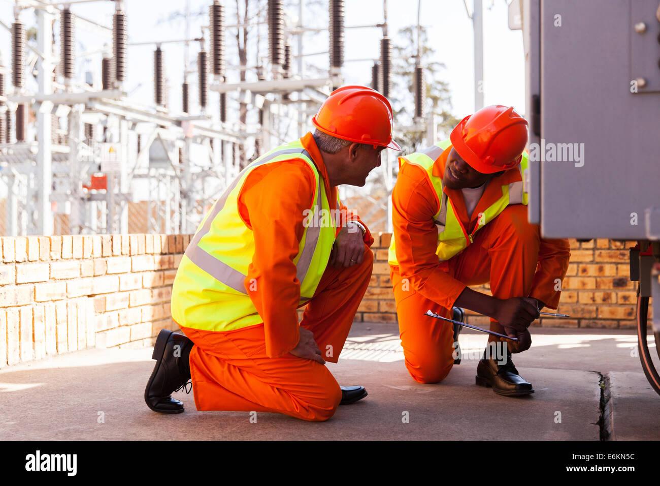 zwei erfahrene Elektriker arbeiten im Umspannwerk diskutieren Stockbild