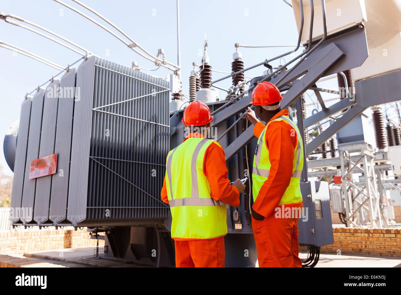 Rückansicht der Elektriker stehen neben einem Transformator im Elektrizitätswerk Stockbild