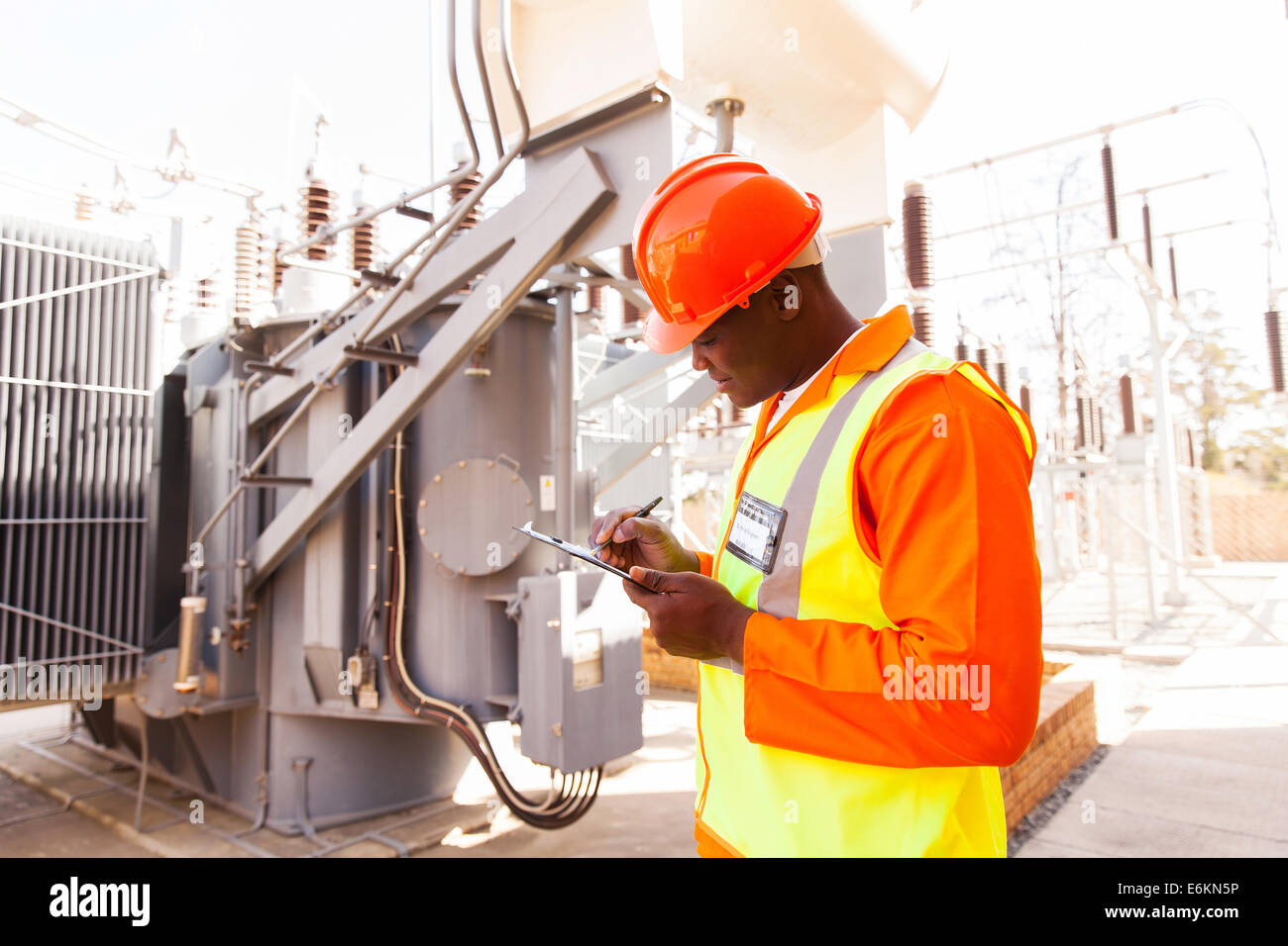 hübscher Afro amerikanischer Elektroingenieur schreiben in Zwischenablage im Kraftwerk Stockbild