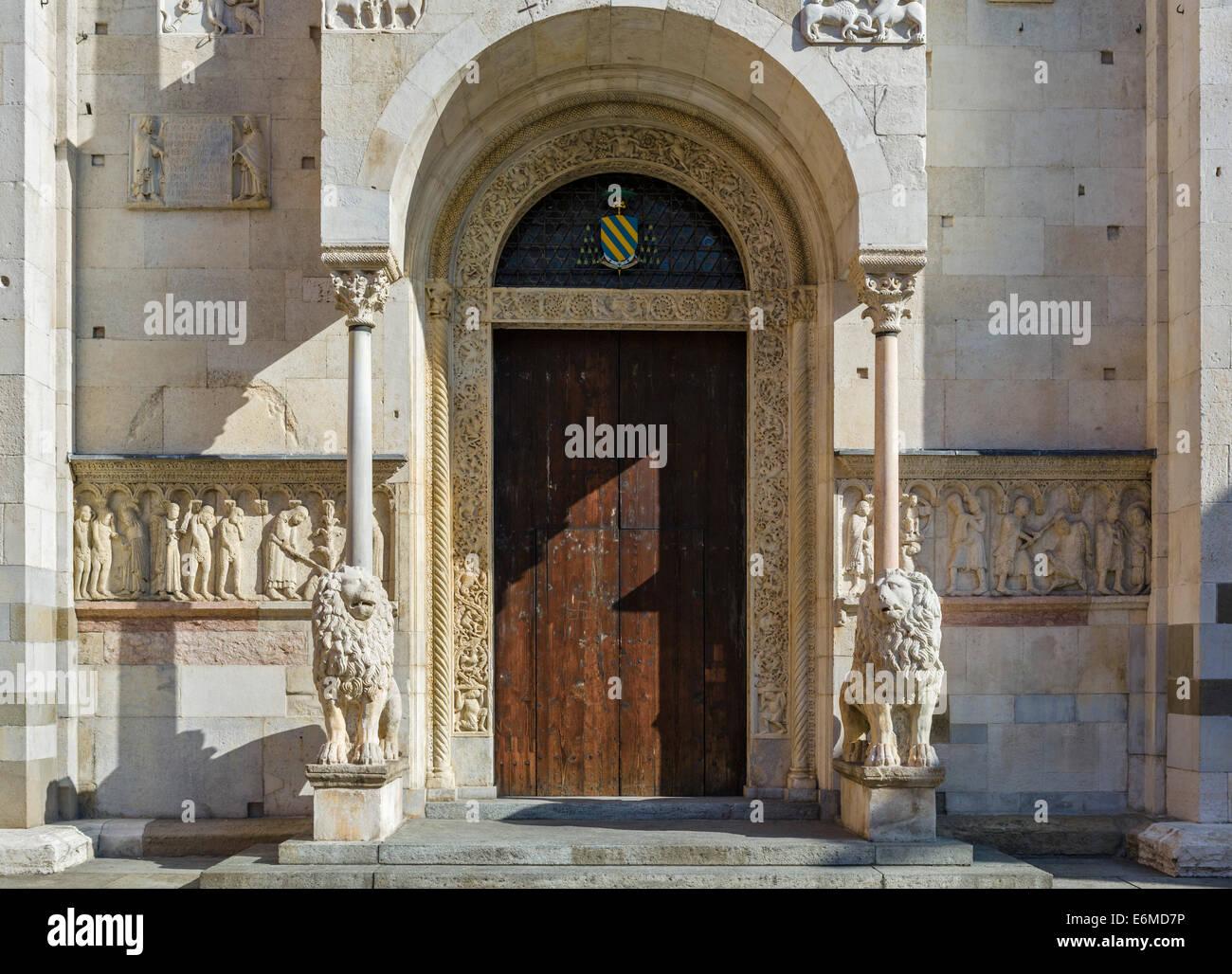 Löwen und Wiligelmo Reliefs durch die Tür in der Westfassade des Duomo, Piazza Duomo, Modena, Emilia Romagna, Stockbild
