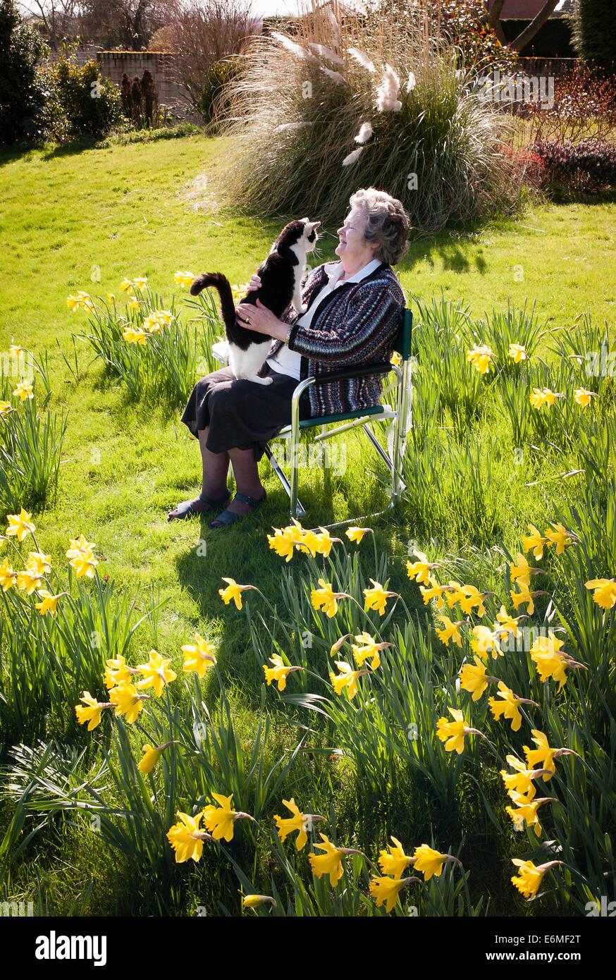 Rentner mit pet-schwarz-weisse Katze in ihrem Frühling Garten. Stockbild