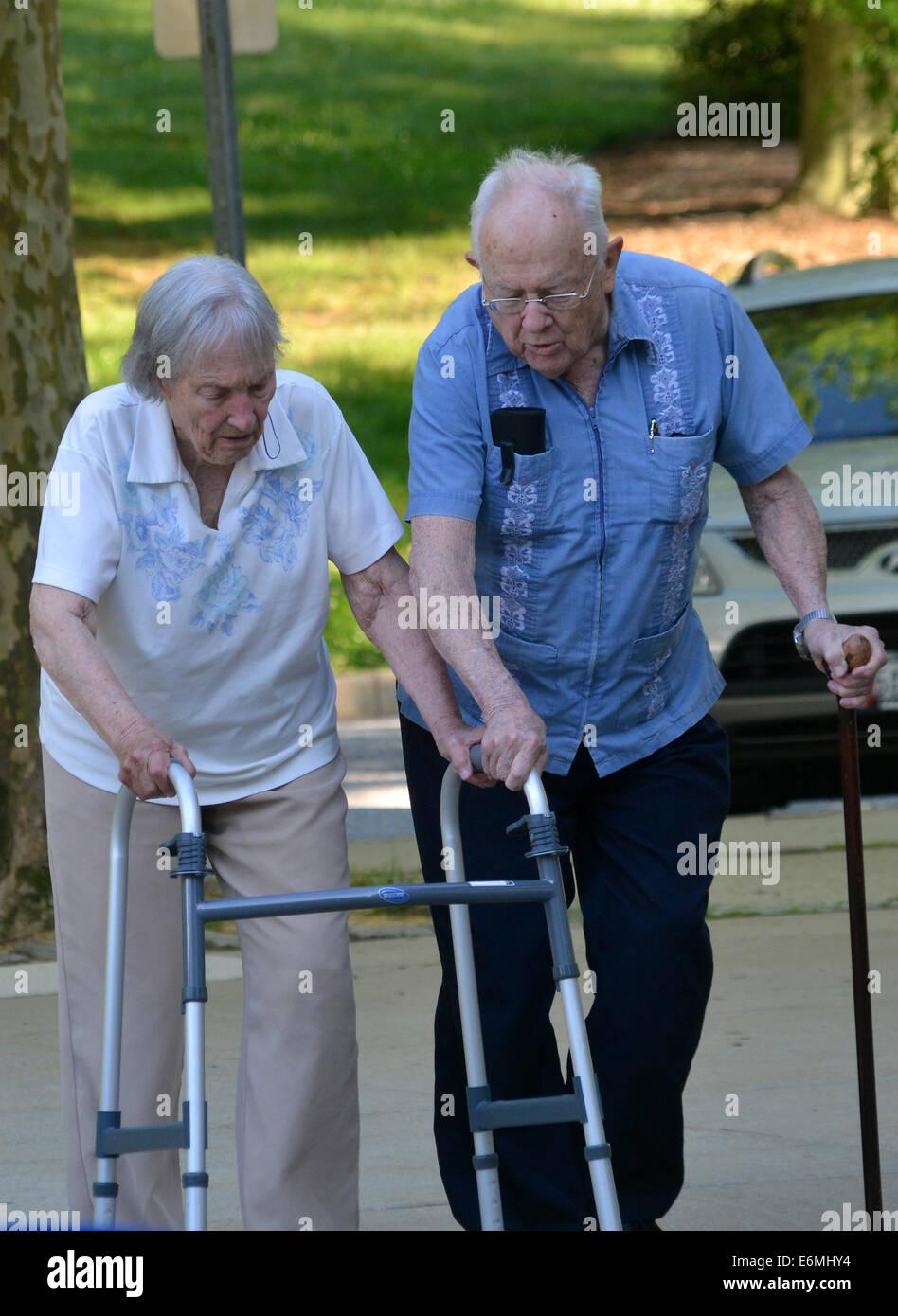 Ein senior Mann hilft seine ältere Frau mit ihrer Gehhilfe Stockbild