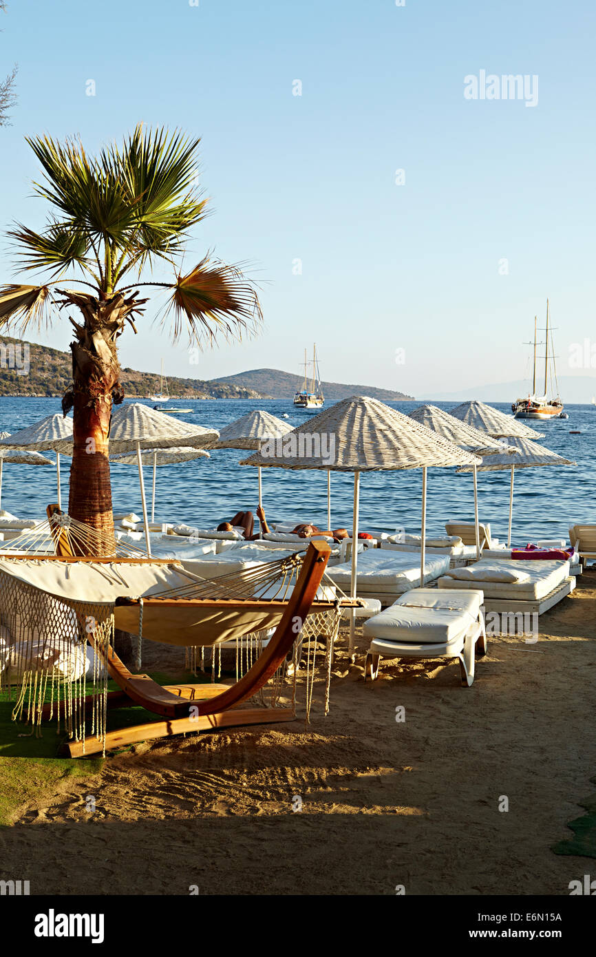 Hängematte am Strand mit weißen Sonnenschirmen und Sonnenliegen, Bitez, Türkei Stockbild