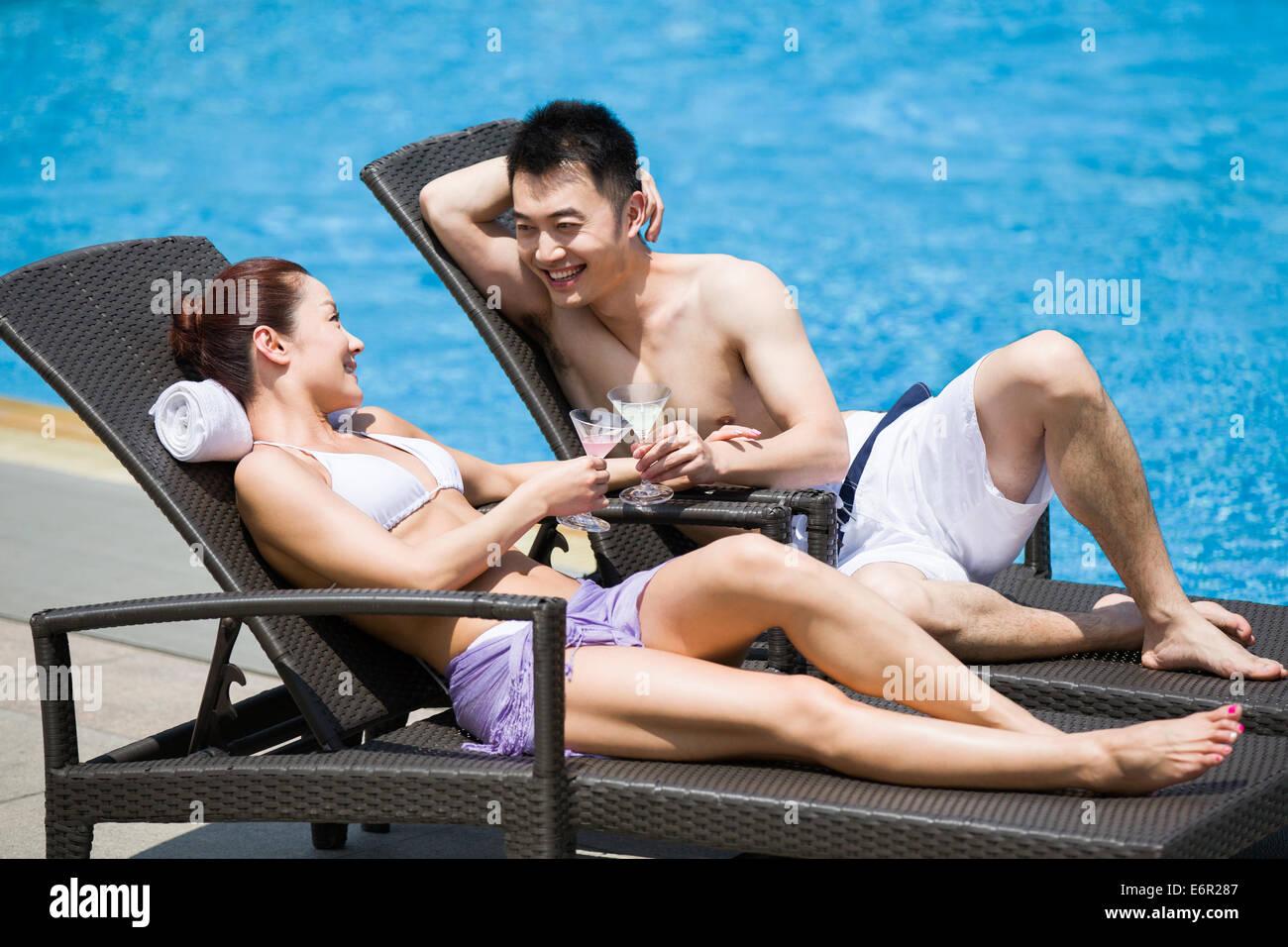 Junges Paar Sonnenbaden am Pool Stockbild