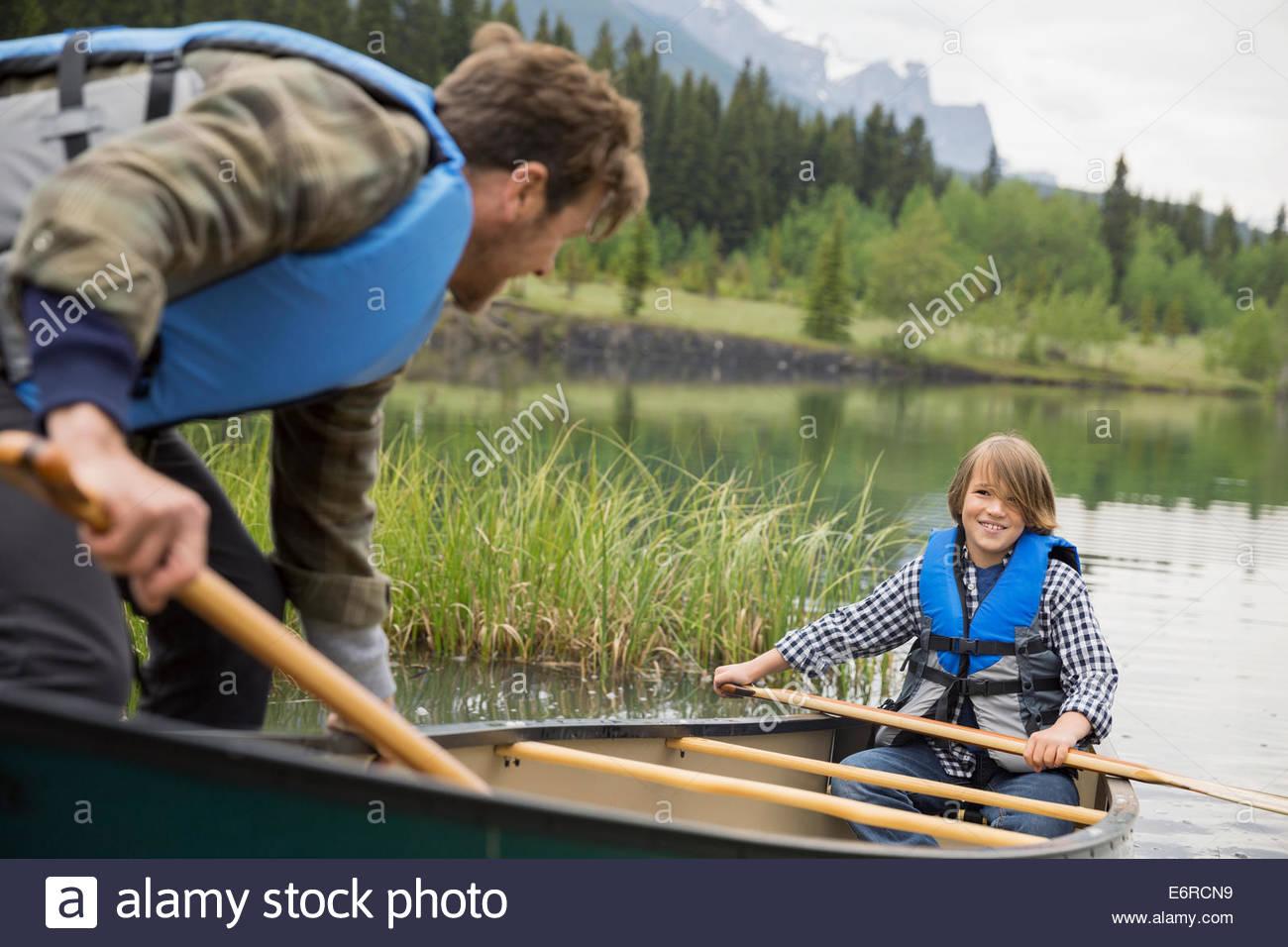 Vater helfen Sohn aus dem Kanu Stockbild