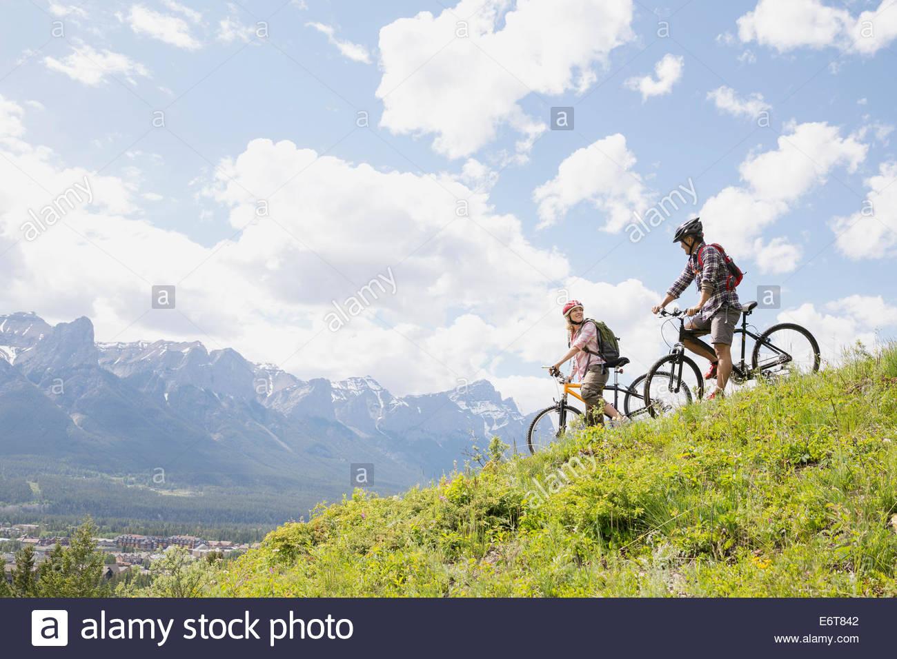 Paar stehend mit Mountainbikes auf Hügel Stockbild