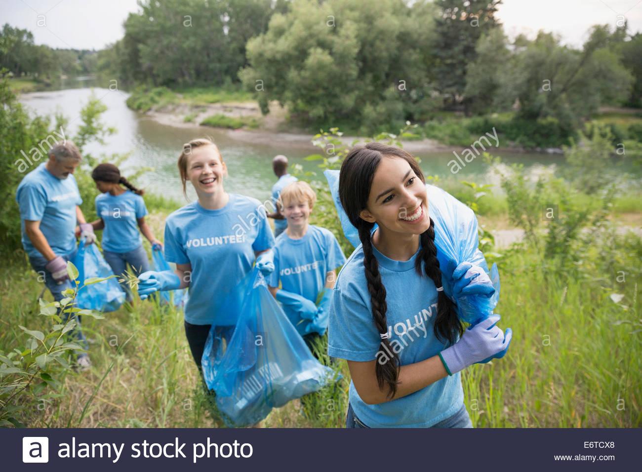Freiwillige tragen Müllsäcke in Feld Stockbild