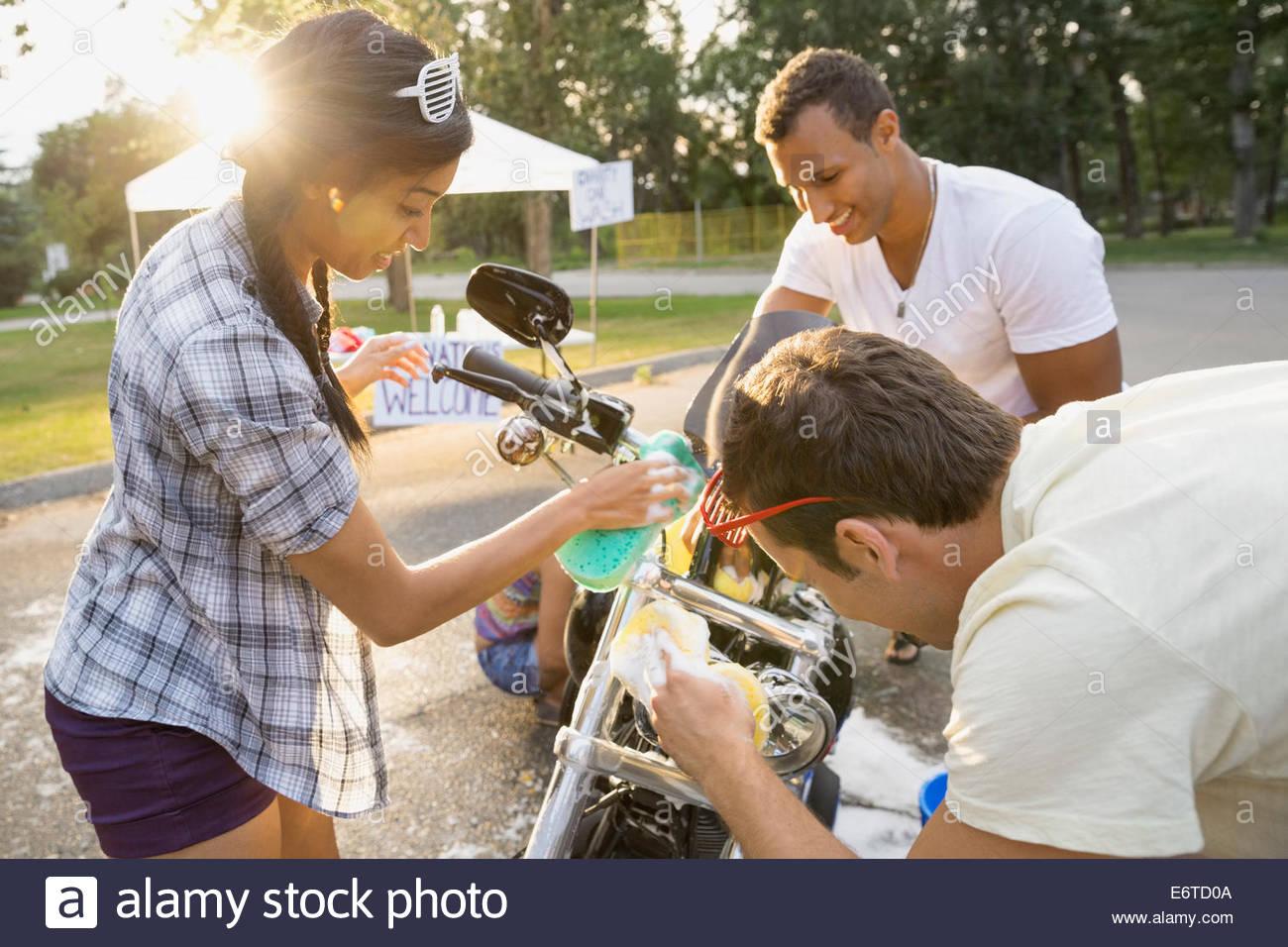 Freunde, die Waschmaschine Motorrad bei Charity-Auto-Waschanlagen Stockbild