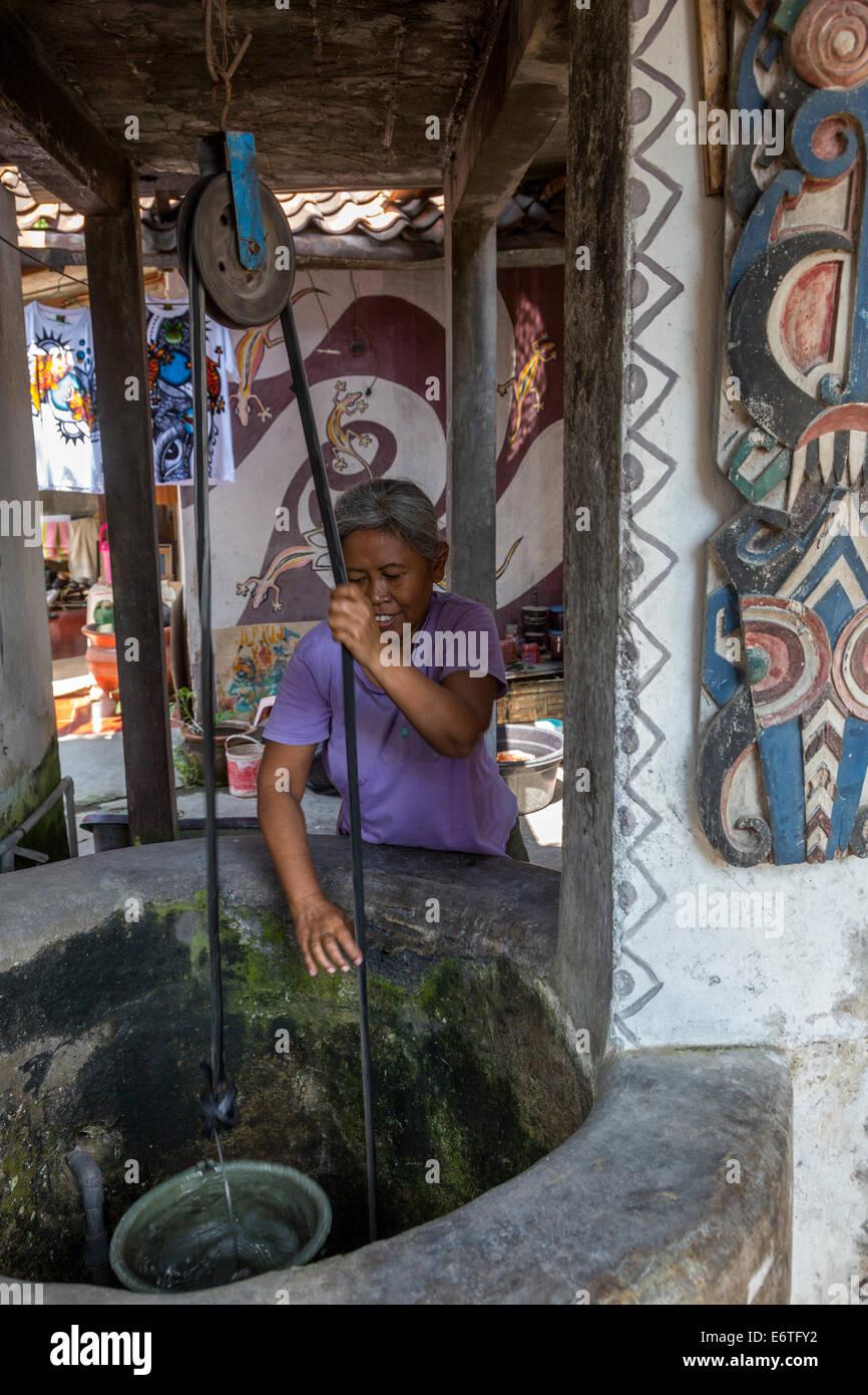 Yogyakarta, Java, Indonesien.  Frau Zeichnung Wasser aus ihrem privaten Brunnen in Nachbarschaft Family Home. Stockbild