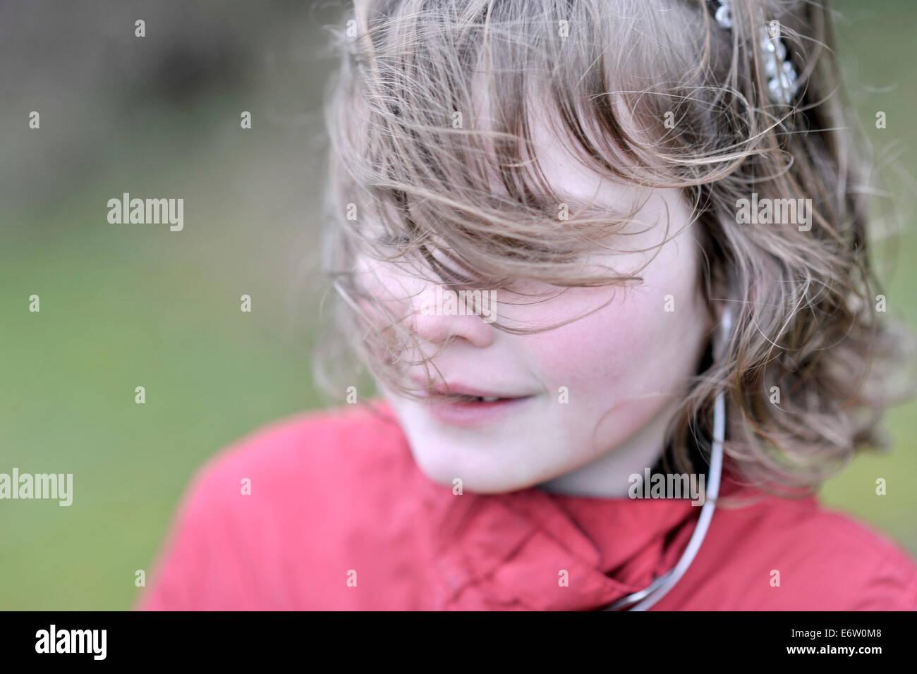sieben Jahre altes Mädchen Musikhören mit Kopfhörer im wind Stockbild
