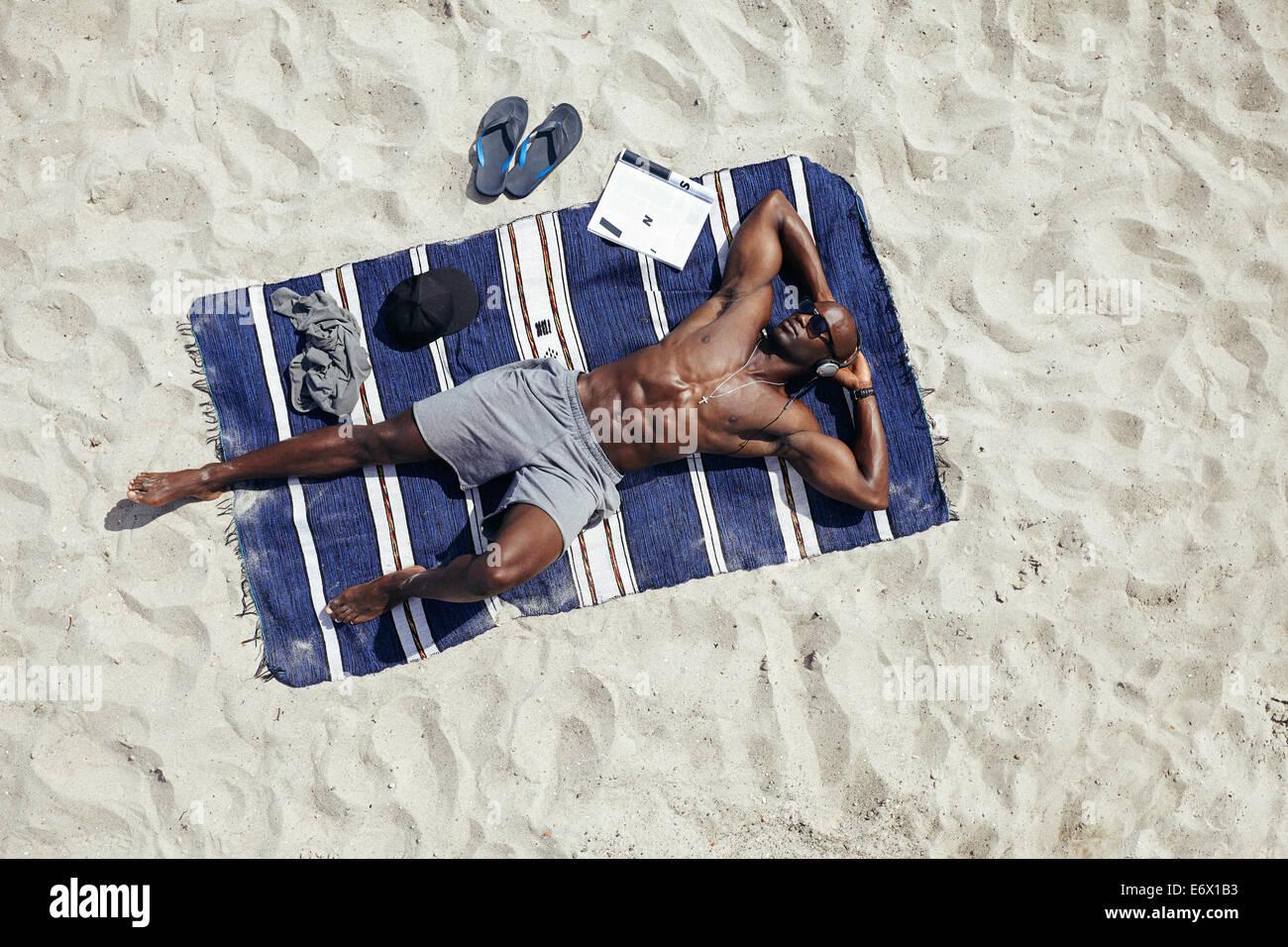 Direkt oben geschossen von muskulösen jungen afrikanischen Kerl Sonnenbaden am Strand. Mann mit Sonnenbrille Stockbild